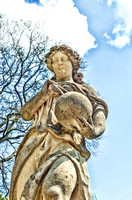 Lady Sculpture With Sphere Against Blue Sky
