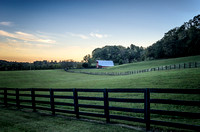 Double row of black fenced field Red barn