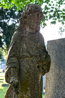 Solemn female sculpture next to headstone
